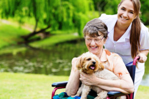 Happy wheelchair-bound woman with pet dog and smiling caregiver