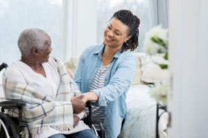 caregiver helping senior woman in a wheelchair