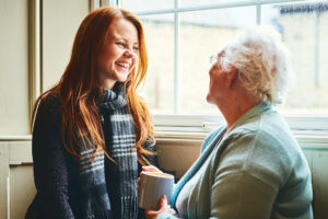 Young woman talking with senior woman about benefits of home care.
