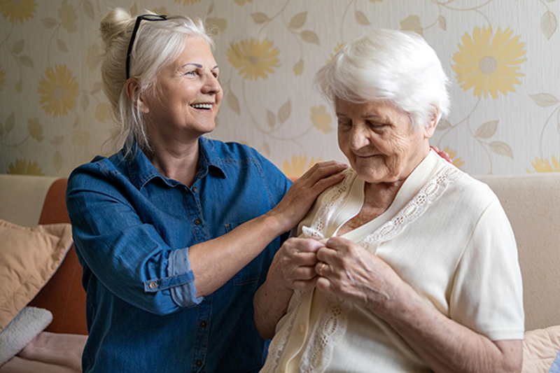 adult daughter caring for mother with middle stages of Alzheimer's