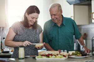 caregiver-assisting-senior-man-make-lunch